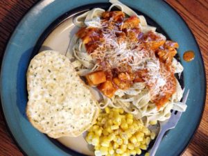 Pasta dinner with garlic bread and corn